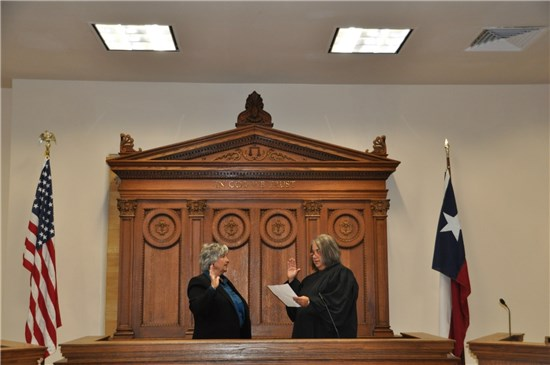 Newly elected County Clerk Dr. Elaine Cardenas (left) is sworn in by Judge Linda Rodriguez.