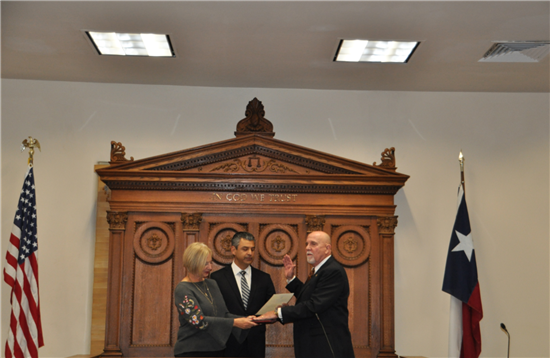County Judge Ruben Becerra (center) swears in re-elected Justice of the Peace Precinct 5 Scott Cary, whose wife Merry holds the Bible.
