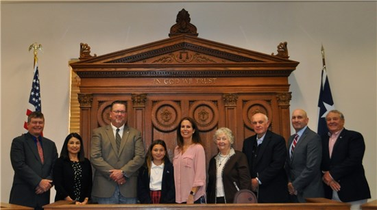 Left to right, joining newly sworn in Precinct 3 Commissioner Lon Shell on the dais following his swearing-in are Precinct 2 Commissioner Mark Jones, Precinct 1 Commissioner Debbie Gonzales Ingalsbe, Justice of the Peace Andy Cable, daughter Katheleen, wife Jennifer, parents Phyllis and Lon R. Shell, Precinct 3 Commissioner Lon Shell, and Precinct 4 Commissioner Ray Whisenant.