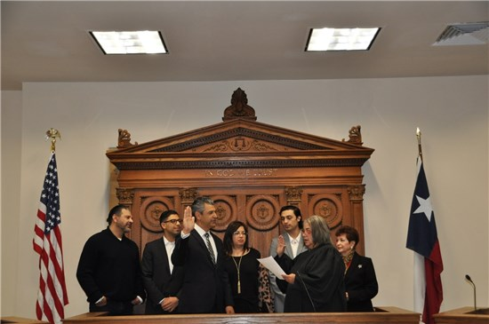 County Judge Ruben Becerra is sworn in by Judge Linda Rodriguez while family members (left to right) brother Joe Becerra, son Ruben Jr., wife Monica Mendez Becerra, son Cristian, and mother Grace Becerra look on.